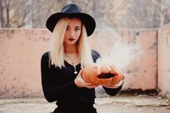 Young woman in the black coat holding the halloween pumpkin with the white smoke coming from inside of it in the autumn. Young woman in the black clothing stock images