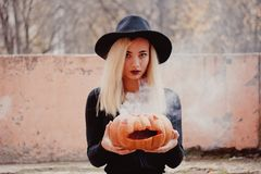 Young woman in the black coat holding the halloween pumpkin with the white smoke coming from inside of it in the autumn stock photography