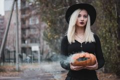 Young woman in the black coat holding the halloween pumpkin with the white smoke coming from inside of it in the autumn. Young woman in the black clothing stock image