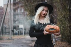 Young woman in the black coat holding the halloween pumpkin with the white smoke coming from inside of it in the autumn. Young woman in the black clothing royalty free stock photography