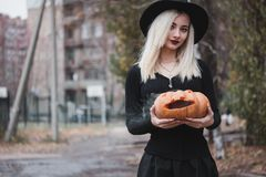Young woman in the black coat holding the halloween pumpkin with the white smoke coming from inside of it in the autumn. Young woman in the black clothing royalty free stock photo