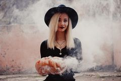 Young woman in the black coat holding the halloween pumpkin with the white smoke coming from inside of it in the autumn. Young woman in the black clothing stock photos