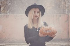 Young woman in the black coat holding the halloween pumpkin with the white smoke coming from inside of it in the autumn stock photo
