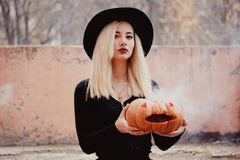 Young woman in the black coat holding the halloween pumpkin with the white smoke coming from inside of it in the autumn. Young woman in the black clothing royalty free stock images