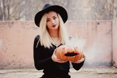 Young woman in the black coat holding the halloween pumpkin with the white smoke coming from inside of it in the autumn royalty free stock photo