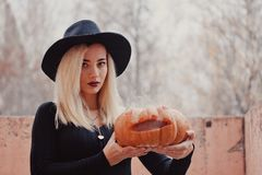 Young woman in the black coat holding the halloween pumpkin with the white smoke coming from inside of it in the autumn. Young woman in the black clothing stock photography