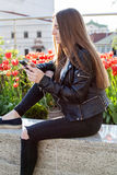 Young woman in black coat and jeans is sitting on the stone parapet Stock Photo