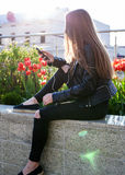 Young woman in black coat and jeans is sitting on the stone parapet Royalty Free Stock Images