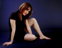 Young woman in a black dress. A photo of a woman sitting on the ground with a black dress and fishnet stockings Stock Photo