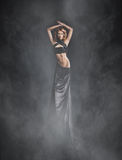 A young woman in a black dress on a foggy background Royalty Free Stock Photo