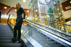 Young woman in a black dress goes on the escalator Stock Image