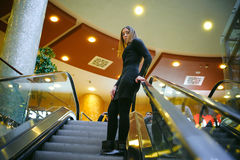 Young woman in a black dress goes on the escalator Royalty Free Stock Image