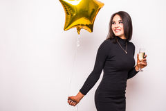 Young woman in black dress with gold star shaped balloon smiling and drinking champagne Royalty Free Stock Images