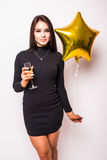 young woman in black dress with gold star shaped balloon smiling and drinking champagne Stock Photography