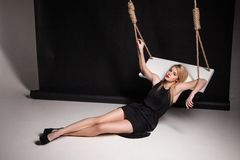 Young woman in black dress half-lying on swing Stock Photos