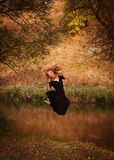 Young woman in black dress jumping Stock Photography