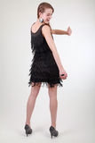 Young woman with black dress looking shy on camera. Young woman in black dress and great earrings has fun and is jaunty dancing in studio in colors, and wearing Stock Photos