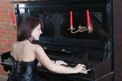 Young woman in black dress playing the piano. Beautiful young woman in black dress playing the piano Royalty Free Stock Photography