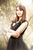 Young woman in black dress posing against bushes Royalty Free Stock Photos