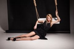Young woman in black dress posing by swing Royalty Free Stock Photography