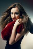 Young woman in black dress with red boa. Young woman in black dress with red fur boa Stock Images