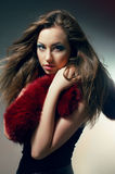 Young woman in black dress with red boa. Young fair woman in black dress with red boa Royalty Free Stock Photography