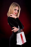 Young woman in black dress with shopping bag. On a dark red background Stock Photos