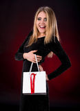 Young woman in black dress with shopping bag. On a dark red background Royalty Free Stock Photos