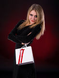 Young woman in black dress with shopping bag. On a dark red background Stock Photo