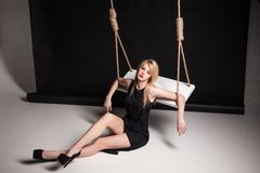 Young woman in black dress sitting by swing Stock Images