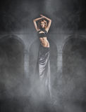 A young woman in a black dress on a spooky background Stock Photography