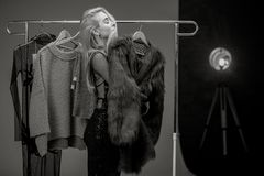 Young woman stands next to rack with hangers and dreams about fur coat. Black and white image. royalty free stock images