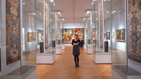 Young Woman in a Black Dress is visitting the Museum and Looks at the Exhibits. Young Woman in a Black Dress Goes through the Museum and Looks at the Exhibits stock footage