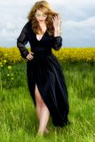 young  woman in black dress in yellow field Stock Photography