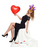 Young woman in black evening gown and carnival mask. Sit on white fur. Heart shaped balloon in hand. Holiday and party concept Royalty Free Stock Images