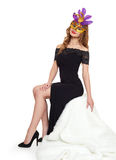 Young woman in black evening gown and carnival mask. Sit on white fur. Holiday and party concept. Royalty Free Stock Image