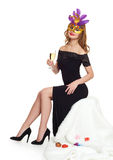 Young woman in black evening gown and a glass of champagne.  Carnival mask on face. Sit on white fur. Holiday and party concept Stock Image