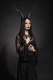 Young woman in black fantasy costume Stock Image