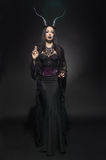 Young woman in black fantasy costume Stock Images