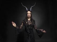 Young woman in black fantasy costume. With big horns on dark background Stock Image