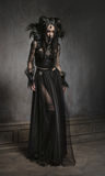 Young woman in black fantasy costume. With feathers on dark background Royalty Free Stock Photos