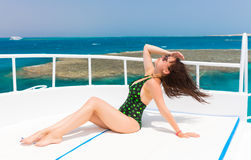 Young woman in black-green swimsuit lying on the deck of the yac Royalty Free Stock Photo