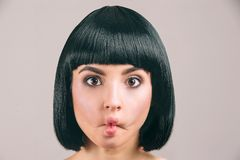 Young woman with black hair posing on camera. Freak brunette model with bob haircut. Holding lips together. Eyes look. Weird. Isolated on light background stock photography