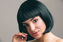 Young woman with black hair posing on camera. Studio shot. Bob haircut. Isolated on light background. Holding piece of royalty free stock photos