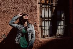Young woman with black hair wearing sunglasses next to a ruined house sunbathing stock photo