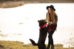 Young woman in black hat have fun with her dog. Image taken on the countryside stock photo