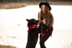 Young woman in black hat have fun with her dog. Image taken on the countryside.  royalty free stock photo