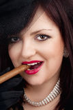 Young Woman with Black Hat Smoking Cigar Royalty Free Stock Photos