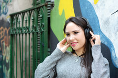 Young woman with black headphones. Outdoors. Royalty Free Stock Photography