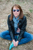 Young woman in a black jacket and jeans sitting on the hay Stock Photo